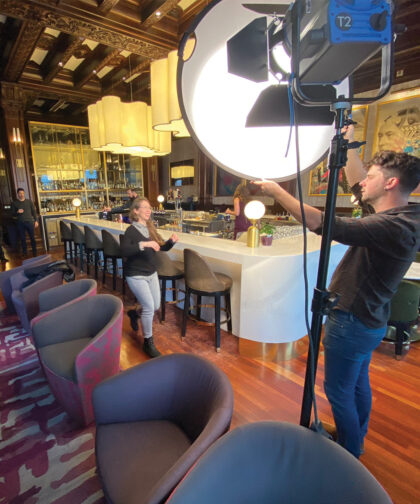 A man adjusts the light in a bar while a woman helps direct.