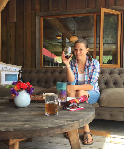 A woman holds a glass of wine while sitting on an outdoor patio.