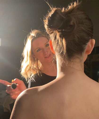 A makeup artist faces the camera as she works on a model, who is facing away from us.