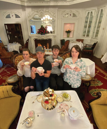 Four people pose holding teacups.