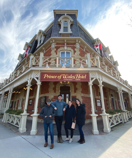 Four people post in front of the Prince of Wales Hotel.