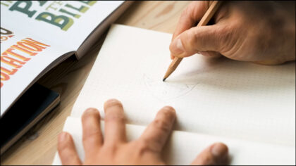 Someone sketches a logo in a notebook.