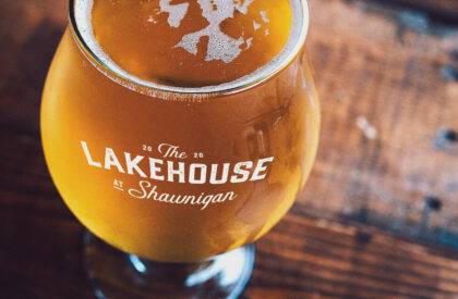 A photo of a glass of beer. The glass is branded with The Lakehouse at Shawnigan.