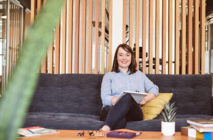 A smiling woman sits cross legged on a couch.