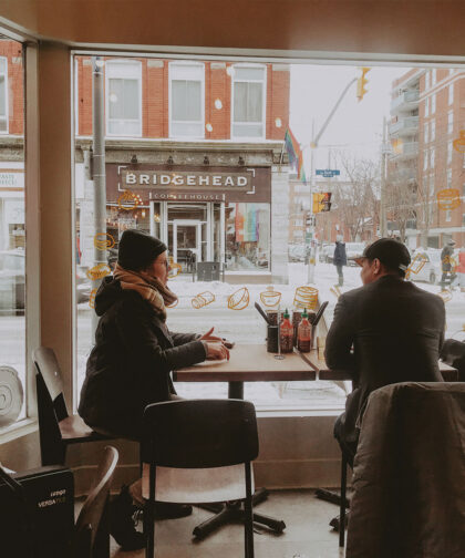 Two people sit a table in a restaurant.
