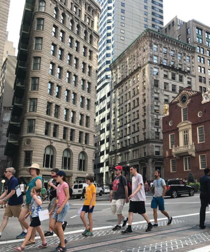 A group of people walk through Boston's streets.