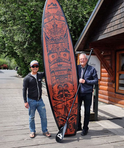 Neil Tran and Jack Julseth stand on either side of a large surfboard decorated with First Nations iconography.