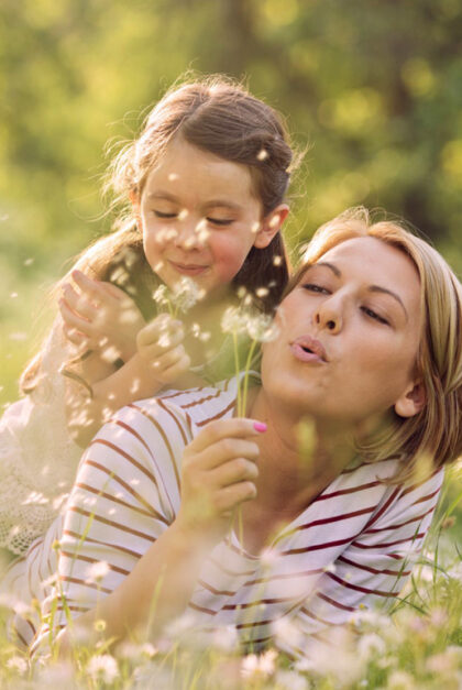 A woman and a girl blow dandelion seeds into the air.