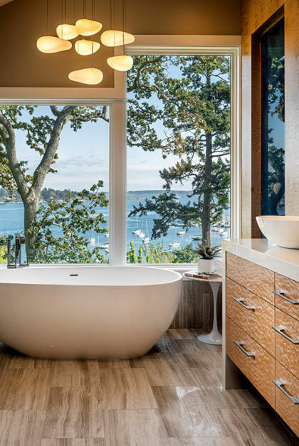 A photo of a bathroom, with a tub set against a window with a view of water, trees, and sailboats.
