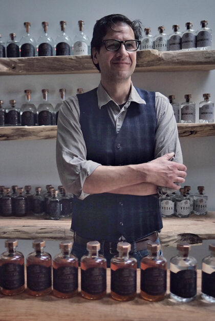 A man stands in front of glass bottles.