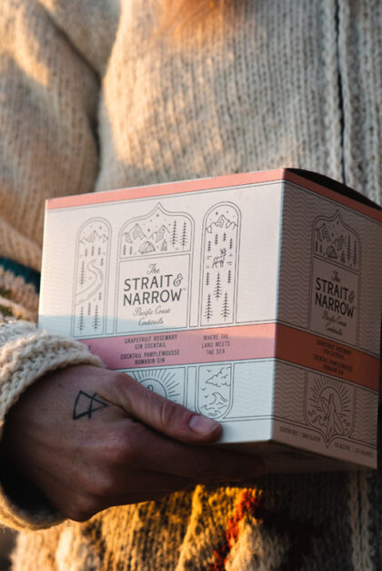 Someone holds in their hand a box of Strait & Narrow drinks.